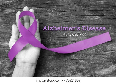 Alzheimer's Disease (AD) Awareness with purple ribbon (clipping path) on human helping hand for World Alzheimers day (month) concept