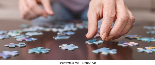 Alzheimer's disease, dementia, memory loss and mental health concept. Hands of old woman with jigsaw puzzle, panorama, close up