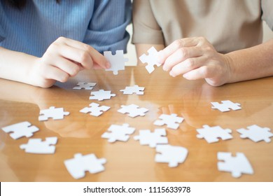 Alzheimer's disease and dementia prevention concept- Elderly and young female playing jigsaw puzzle together on wooden table at home. Activity can improve brain function. Mental health. Close up.