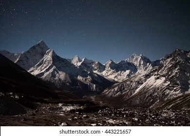 Ama Dablam mountain panoramic view on a starry night. Beautiful night mountain landscape under bright moonlight. Stars above himalayan mountain range, Everest Base Camp Trek, Himalayas, Nepal.