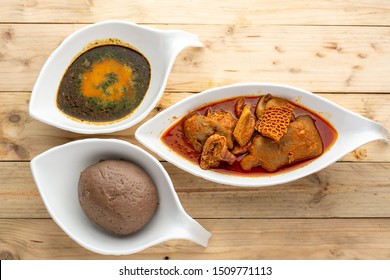Amala with Ewedu and assorted meat stew in 3 ceramic bowls on a wooden background from an overlay perspective