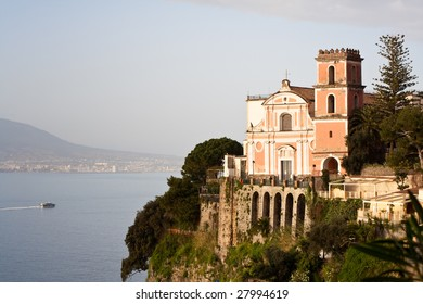 Amalfi Coast : church on a cliff directly above sea. Mount Vesuvius on the background. Town Vico Equense
