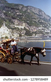 AMALFI, ITALY, 1992 - A patient horse pulls the wheelchair with two tourists on board and the coachman in the splendid panorama of the Amalfi Coast