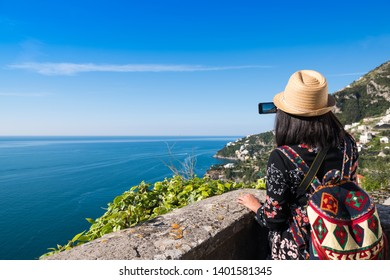 Amalfi, Italy - April 19, 2019:  Traveler woman with backpack photographing beautiful Italian coast.