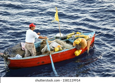 AMALFI, ITALY-OCT. 8, 2008:  An Italian fisherman rows out to sea in his small fishing boat hoping to catch his evening dinner.