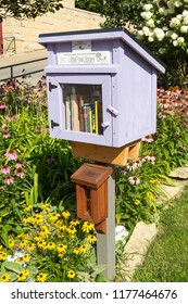 AMANA IOWA USA. JULY 29 2018. Free Little Library Take a Book and Leave a Book  wooden box in a garden setting.