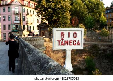 AMARANTE, PORTUGAL - September 23, 2017: Tourist crossing the Bridge of Sao Goncalo over the Tamega River in Amarante, Portugal