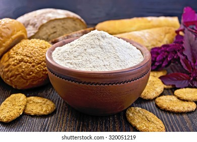 Amaranth flour in a clay bowl with bread and biscuits, purple flower on the background of wooden boards