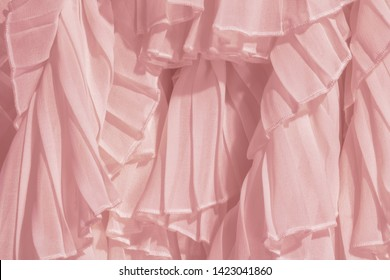Amaranth pink color chiffon fabric folds. Rose dress with ruffles and frills.