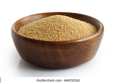 Amaranth seeds in dark wooden bowl isolated on white.