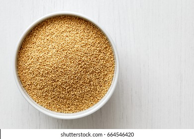 Amaranth seeds in white ceramic bowl isolated on painted white wood from above.