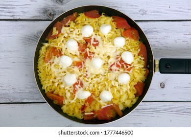 Amaranth spaghetti with tomatoes, mozzarella and parmesan in a pan