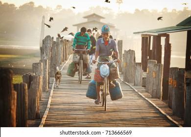 AMARAPURA, MYANMAR (BURMA) - December, 2014: Man on the bicycle crossing U Bein wooden bridge, front view, Amarapura, Myanmar (Burma) on December, 2014