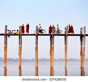 AMARAPURA, MYANMAR - JANUARY 12, 2011: Local people and tourists walking on famous U Bein teak bridge in Amarapura, Mandalay Division of Myanmar