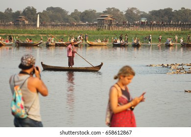 Amarapura,Myanmar - February 20 2016 : View around U-Bein bridge with Man punting in lake,tourists boat and tourists walking taking pictures around there.