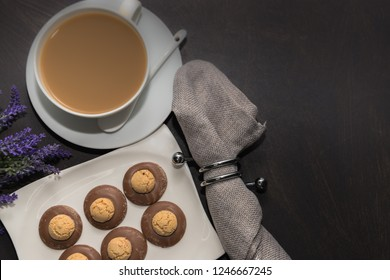 Amaretti cookies in chocolate on a white plate. Cup of coffee with milk. Dark background, free space, top view