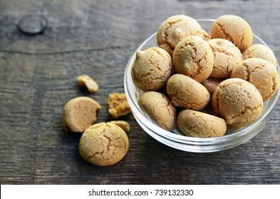 Amaretti cookies in a glass bowl on old wooden background.Italian amarettini biscuits.