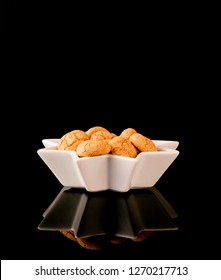 Amaretti traditional italian almond cookies. Christmas & new year cookies amaretti in a white star shaped bowl on a black glossy background with reflection.- Image