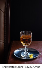 Amaretto, Brandy, Whiskey, or a Brown Liqueur Cocktail Drink with Lemon Twist in Dark Bar with Leather Seats
