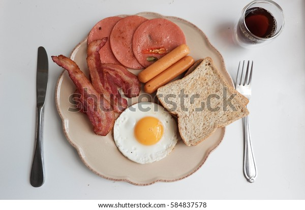 Amarican breakfast with fried egg, bacon, toast, ham,sausages  and coffee, white background