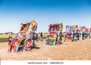 Amarillo, Texas / USA - July 24, 2019: Cadillac Ranch, located along I-40, is a public art sculpture of antique Cadillacs buried nose-down in a field.