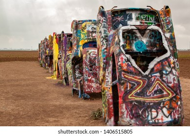 Amarillo, United States - July 6, 2006: A row of Cadillac's buried face down in the dirt spray painted by visitors.