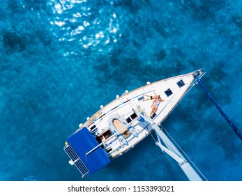 Amasing aerial view to Yacht in deep blue sea with relaxing kids. Drone photography