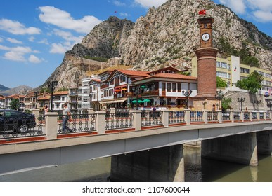 Amasya, Turkey - June 7, 2018: Old Ottoman houses and clock tower view by the Yesilirmak River in Amasya City.