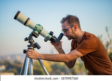 Amateur astronomer looking at the sky with a telescope.