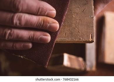 Amateur carpenter uses sandedpaper on wood