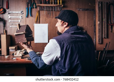 Amateur carpenter with wooden birdhouse in workshop