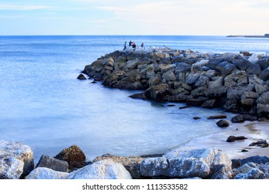 Amateur fishermen on a breakwater structure along the coastal area around Oeiras, Portugal