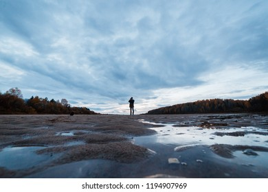 Amateur landscape photographer shooting the evening autumn scenery of the river. Landscape therapy concept.