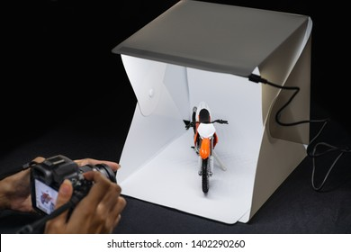 Amateur photographer working on mirrorless camera to shooting motrocycle model in mini lightbox