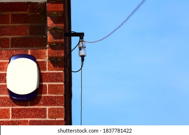 Amateur radio long wire HF dipole antenna and balun fixed to the side of a house wall