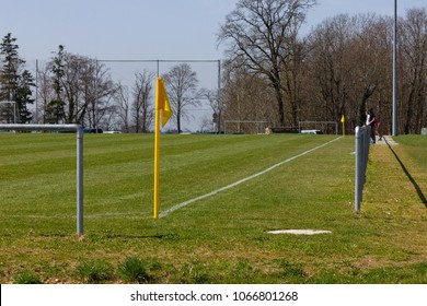 amateur soccer field with green lawn and white lines with yellow pole on the corner edge