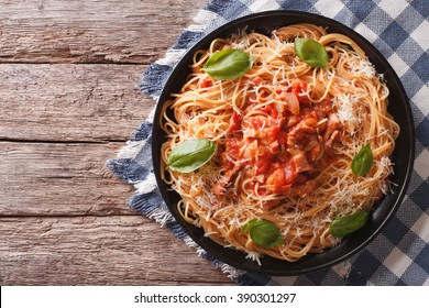 Amatriciana Spaghetti with cheese and basil on a plate on the table. horizontal top view