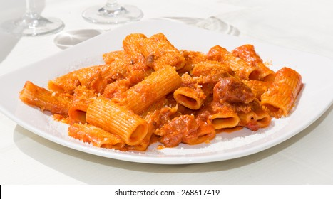 Amatriciana: traditional italian pasta with pork cheek and tomato sauce served with grated cheese