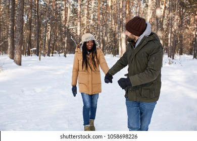 Amazed African American couple. International couple in the winter forest