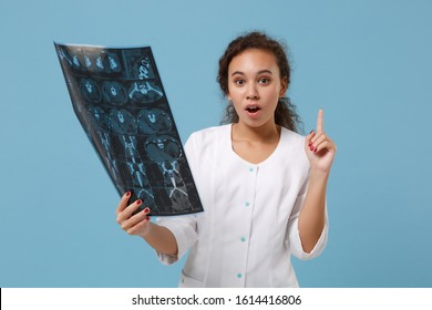 Amazed african american doctor woman in medical gown holding x-ray the brain by radiographic image ct scan mri isolated on blue background. Healthcare personnel medicine concept. Mock up copy space