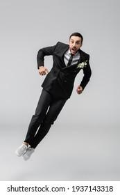 Amazed arabian groom jumping isolated on grey