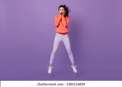 Amazed asian woman looking at camera. Studio shot of jumping surprised chinese girl.