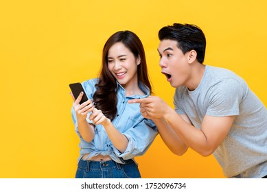 Erstaunlich attraktives junges asiatisches Paar mit Blick auf Smartphone einzeln auf gelbem Studiohintergrund
