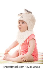Amazed baby girl with fluffy bunny ears hat looking away