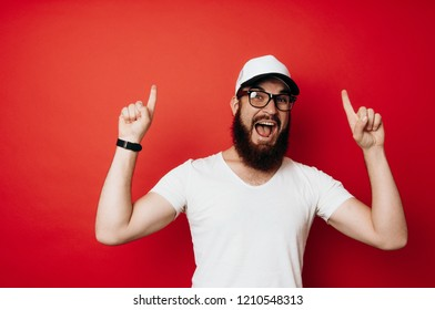 Amazed bearded man pointing up over red background