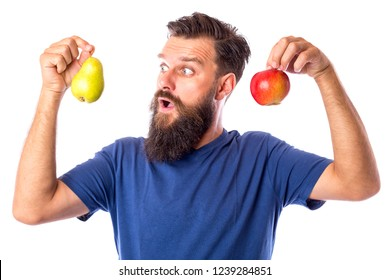 Amazed bearded young man holding a ripe two fruits, a pear and an apple, over white background