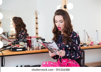 Amazed beautiful young woman sitting in beauty salon and reading fashion magazine