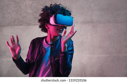 Amazed black teen girl in modern Vr headset gesturing with hand and looking away while standing near concrete wall