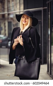 Amazed blondie bimbo looking up with her mouth ajar, having surprised look on delicate face. Carrying her over-sized designer handbag on arm, holding her jacket on her shoulders.