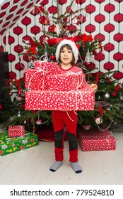 Amazed boy holding many Christmas presents  in front of tree